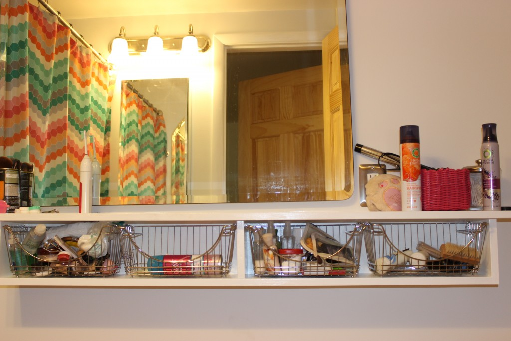 Because 3 girls are sharing this bathroom, Builder built this shelf, and the girls found baskets to hold their things